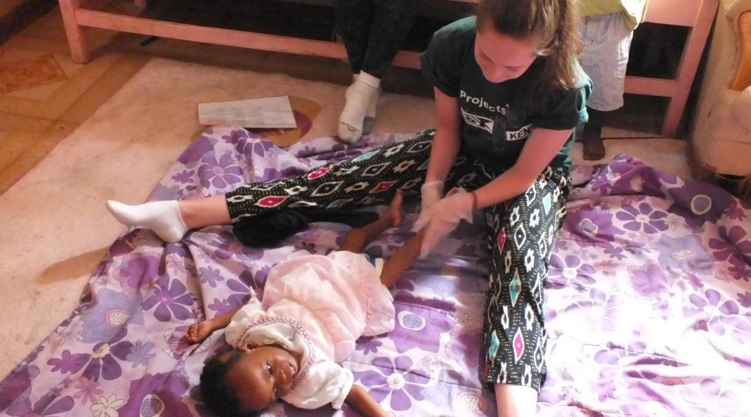 A Projects Abroad volunteer doing an Occupational Therapy internship in Kenya works on a baby's routine.